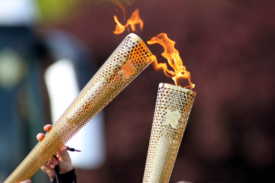 the history of olympic torch The olympic torch is meant to symbolize the fire gifted to mankind by prometheus in greek mythology today's torch is also used as a symbol to connect the ancient games with their modern counterpart.