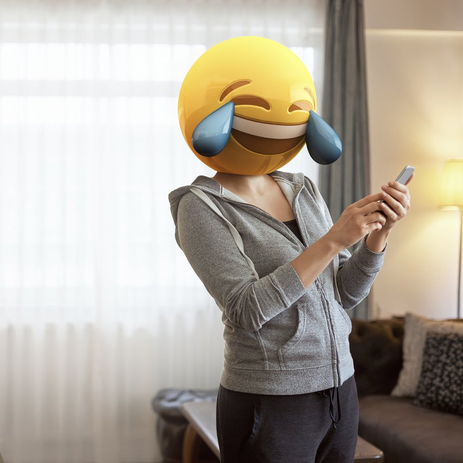 Woman wearing emoji masks while looking at her phone